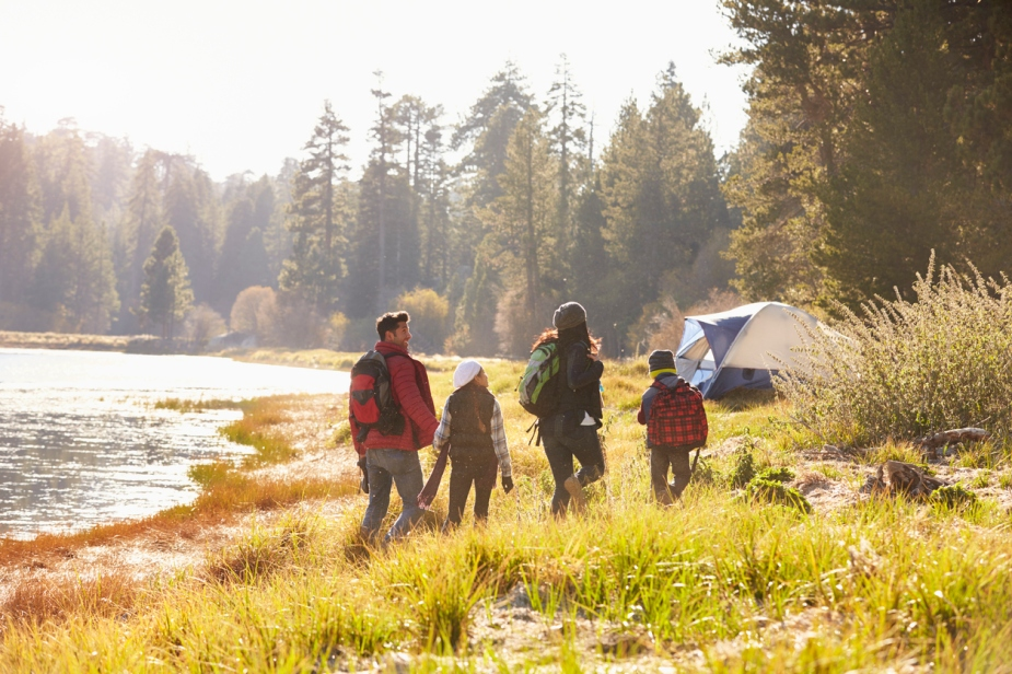 Family on a camping trip walking near a lake, back view